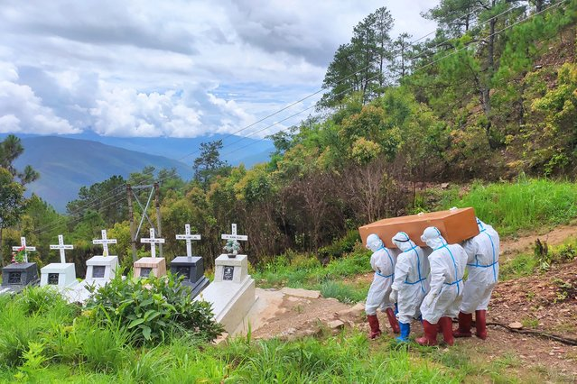 This handout photo from local media group Chinland Herald Daily News taken on June 21, 2021 and released on June 22, shows health workers in protective suit carrying a coffin bearing a body of a Covid-19 coronavirus patient during a burial at a cemetery in Falam township in western Myanmar's Chin state. (Photo by Chinland Herald Daily News via AFP Photo)