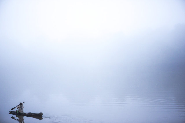 A Poti-Krô villager leaves in the early morning fog to check his nets for fish. (Taylor Weidman)