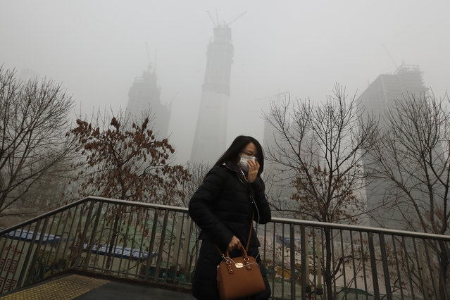 A woman holds her mask for protection against air pollution on a pedestrian overhead bridge in Beijing as the capital of China is shrouded by heavy smog on Tuesday, December 20, 2016. Thick, gray smog fell over Beijing on Tuesday, clouding China's capital in a haze that spurred authorities to cancel flights and close some highways in emergency measures to cut down on air pollution. (Photo by Andy Wong/AP Photo)