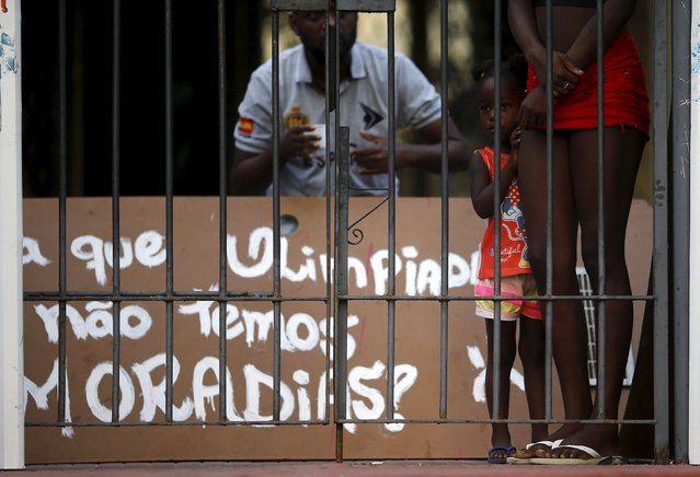 Squatters look on from inside an abandoned building in Flamengo neighborhood, before its eviction in Rio de Janeiro April 14, 2015. Dozens of riot police removed squatters from a derelict building in Rio de Janeiro, which was supposed to be turned into a luxury hotel for the Olympic Games by Brazil's once-richest-man Eike Batista, whose oil and mining empire collapsed. (Photo by Ricardo Moraes/Reuters)