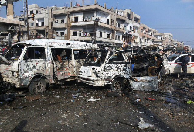 In this photo released by the Syrian official news agency SANA, Syrian citizens gather at the scene where two blasts exploded in the pro-government neighborhood of Zahraa, in Homs province, Syria, Sunday, February 21, 2016. Two blasts in the central Syrian city of Homs killed more than a dozen people and injured many others in the latest wave of violence to hit the city in recent weeks, state TV said. (Photo by SANA via AP Photo)
