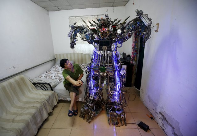 Chinese inventor Tao Xiangli controls his home-made humanoid robot with a remote controller as he poses with it during a photo opportunity at his house located in a old residential area in Beijing in this August 8, 2013 file photo. (Photo by Kim Kyung-Hoon/Reuters)