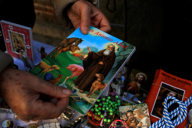 A woman buys a book after a mass outside San Anton Church in Madrid, Spain, January 17, 2017. (Photo by Juan Medina/Reuters)