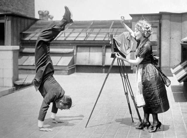 Mary Pickford takes a picture of husband Douglas Fairbanks, Sr., who is executing a handstand on the roof of a building on December 19, 1920. (Photo by Bettmann Archive/Getty Images)