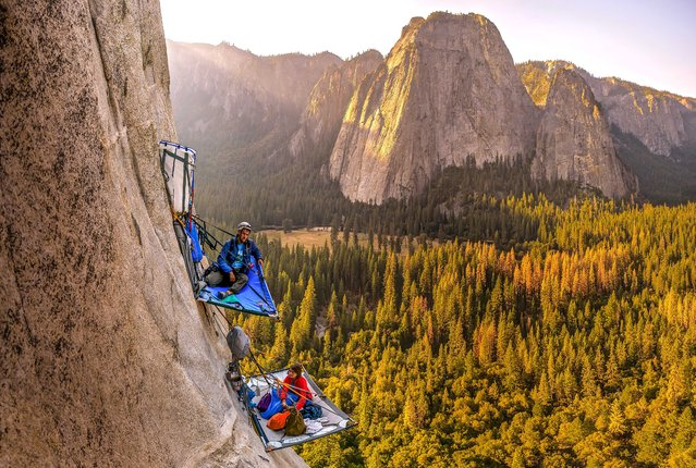 Morgane Choquet and Samuel Cobb relax in a vertical campsite on the slopes of El Capitan, Yosemite National Park. (Photo by Alexandre Eggermont/Caters News Agency)