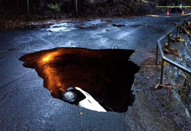 A pickup truck sits in a sinkhole-like crater after a road collapsed due to heavy rains near Paauilo, on the big island of Hawaii, December 30, 2013. The driver of the truck escaped with minor injuries. (Photo by Kaipo Honda/Reuters)