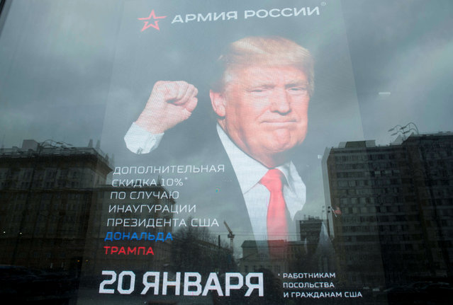 """The U.S. Embassy building is reflected in a window of a Russian military outerwear shop """"Armia Rossii"""" (Russian Army) displaying a poster of Donald Trump, in downtown Moscow, Russia, Friday, January 20, 2017, hours ahead of Donald Trump being sworn in as president of the United States, The poster reads: """"10 percent discount to the embassy employees and US citizens on the Inauguration Day"""". (Photo by Pavel Golovkin/AP Photo)"""