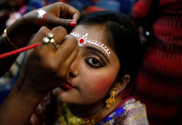 A bride gets her makeup done before the start of a mass marriage ceremony in which, according to its organizers, 160 Hindu, Muslim and Christian couples will take their wedding vows on Valentine's Day, in Kolkata, India on February 14, 2019. (Photo by Rupak De Chowdhuri/Reuters)