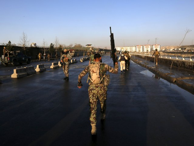 An Afghan security forces holds up his rifle as he walks at the site of an attack in Kabul, Afghanistan February 27, 2016. A loud explosion rocked the Afghan capital Kabul near the defence ministry on Saturday, hours after a suicide bomber killed at least 11 people in the eastern province of Kunar. (Photo by Mohammad Ismail/Reuters)