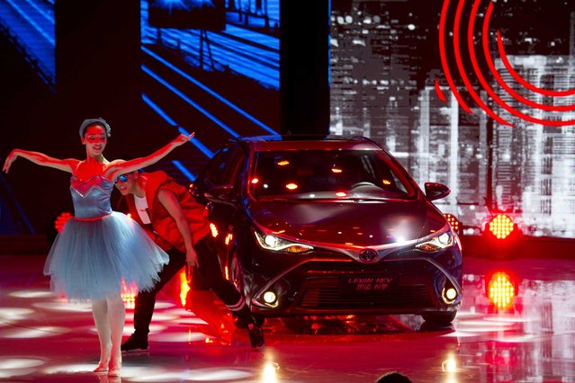 Dancers introduce the latest car from Japanese automaker Toyota at the Shanghai Auto Show in Shanghai Monday, April 20, 2015. (Photo by Ng Han Guan/AP Photo)