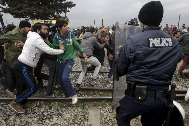 Stranded refugees and migrants try to break a Greek police cordon in order to approach the border fence at the Greek-Macedonian border, near the Greek village of Idomeni, February 29, 2016. (Photo by Alexandros Avramidis/Reuters)