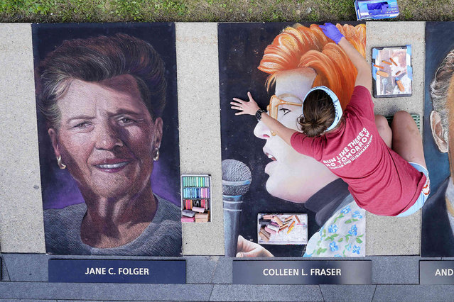 Chalk artist Erica LuBer, from Allentown, Pa., works on a chalk portrait of Colleen Fraser, from Elizabeth, N.J., who was one of the 40 passengers and crew who perished on Flight 93, outside the Flight 93 National Memorial on Thursday, September 9, 2021, in Shanksville, Pa., as the nation prepares to mark the 20th anniversary of the Sept. 11, 2001 attacks, Saturday, Sept. 11, 2021. A group of 11 chalk artists from around the country worked on the forty portraits for two days outside the Flight 93 National Memorial. (Photo by Gene J. Puskar/AP Photo)