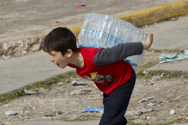 A child carries bottles of water  at the old airport in Athens, Greece, Tuesday, March 1, 2016. Border restrictions further north in the Balkans have left thousands of refugees and other migrants stranded in a country that is still wracked by its own financial crisis and unable to seal its lengthy sea border with Turkey. (Photo by Vadim Ghirda/AP Photo)