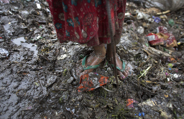 An Indian girl stands at a garbage dump area on the outskirts of Gauhati, India, Wednesday, April 22, 2015. (Photo by Anupam Nath/AP Photo)