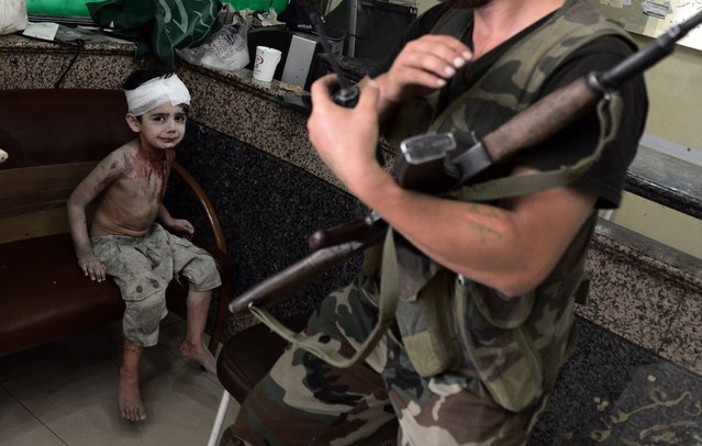 A Syrian boy who was injured when a shell, released by regime forces, hit his house on August 24, 2012, waits to be treated at a hospital in Syria's northern city of Aleppo. (Photo by Aris Messinis/AFP Photo)