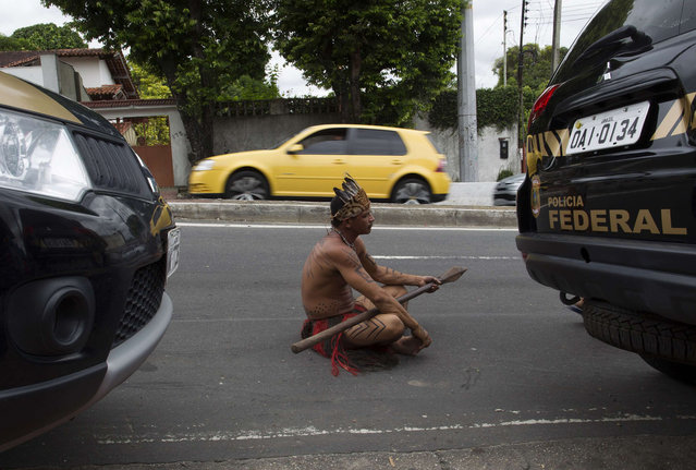 An Amazon Indian sits on the street in front of the headquarters of Brazil's Indian affairs bureau FUNAI after police expelled by court order a group of Indians who were occupying the building, in Manaus January 29, 2014. (Photo by Bruno Kelly/Reuters)