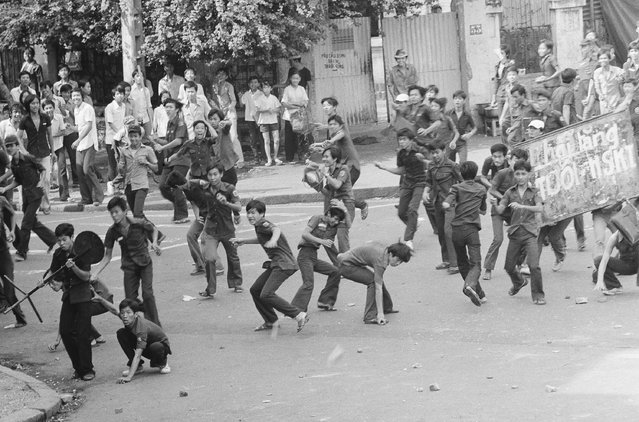 Rock throwing Saigon middle school students charge police during an anti-draft demonstration in Saigon, Thursday, March 27, 1975. The students were angered by changes in the conscription law, lowering the draft age to 17. The change came about due to the increasingly serious military situation. (Photo by Lo Vinh/AP Photo)
