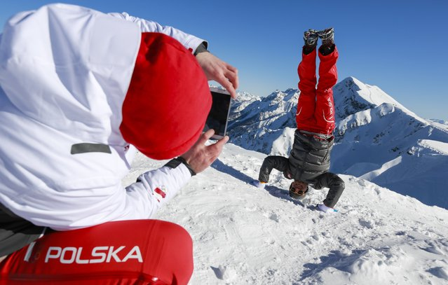 Polish bobsledder Pawel Mroz, left, takes a snapshot of luger Karol Mikrut of Poland on Rosa Peak, 2320 meters above sea level, at Rosa Khutor ski resort in Krasnaya Polyana, Russia ahead of the Sochi 2014 Winter Olympics, Thursday, February 6, 2014. (Photo by Gero Breloer/AP Photo)