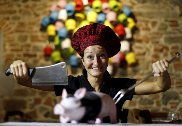"Italian chef Cristina Palanti poses with a meat cleaver and cooking fork hovering over a plastic pig figurine at the ""L'e'Maiala"" restaurant in Florence in this October 6, 2012 file photo. Florence is the latest Italian tourist destination to adopt the mantra ""you are what you eat"", and is requiring shops and restaurants to make sure that 70 percent of their food comes from the surrounding region. (Photo by Alessandro Bianchi/Reuters)"