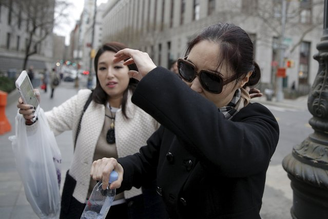 Julia Vivi Wang, (R) who is accused of having paid a bribe for diplomatic positions, attempts to shield herself as she exits the Manhattan U.S. District Courthouse in New York March 18, 2016. The broad United Nations corruption investigation that swept up a former president of the General Assembly expanded on Friday, as federal prosecutors charged a Chinese-born executive with paying at least $500,000 in bribes to buy diplomatic positions with the government of Antigua for her husband and another man. (Photo by Brendan McDermid/Reuters)