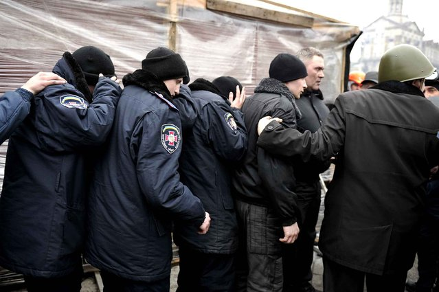 Anti-government protesters talk to policemen who were captured during clashes with riot police in central Kiev on February 20, 2014. (Photo by Louisa Gouliamaki/AFP Photo)
