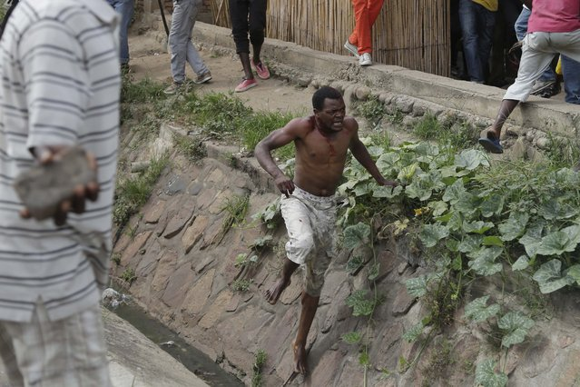 Jean Claude Niyonzima, a suspected member of the ruling party's Imbonerakure youth militia, flees from his house into a sewer under a hail of stones thrown by a mob protesting against President Pierre Nkurunziza's decision to seek a third term in office, in the Cibitoke district of Bujumbura, Burundi, Thursday May 7, 2015. (Photo by Jerome Delay/AP Photo)