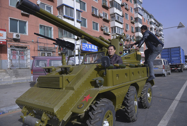 A man surnamed Zhang sits in his home-made armored vehicle look-alike on a street in Shenyang, Liaoning province, November 12, 2014. Zhang and his friends converted two cars into these two vehicles for his son, and will be displaying them on show at a local park. The cannons on the vehicles can fire paintballs and smoke shells, local media cited Zhang as saying. (Photo by Reuters/Stringer)