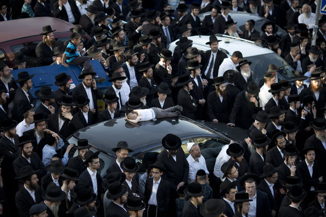Ultra-Orthodox Jews watch the funeral procession of Rabbi of the Kaliv Hasidic dynasty and Holocaust survivor Menachem Mendel Taub during his funeral in Jerusalem, Sunday, April 28, 2019. Thousands attended the Jerusalem funeral of Menachem Mendel Taub, scion of a Hungarian rabbinic dynasty, who died Sunday aged 96. Taub helped produce a two-volume encyclopedia documenting Jewish religious martyrs killed in the Holocaust. His death comes days before Israel marks Holocaust Remembrance Day, honoring six million Jews killed by Nazi Germany. (Photo by Ariel Schalit/AP Photo)