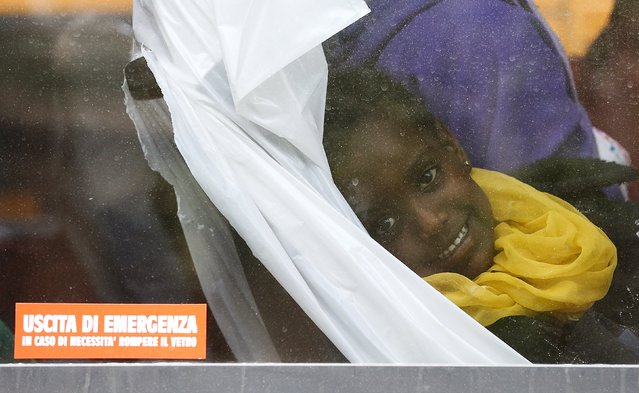 A child smiles from the window of a bus after she disembarked from the Migrant Offshore Aid Station (MOAS) ship MV Phoenix in the Sicilian harbour of Messina, Italy May 16, 2015. (Photo by Antonio Parrinello/Reuters)