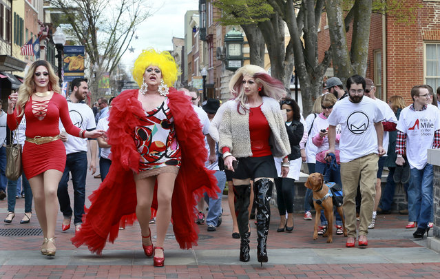 """Drag queens Alexa Shontelle, from left, Stephanie Michaels and Buffy Tanglewood lead the walkers in the Laurel Center's first """"Walk a Mile in Her Shoes"""" event held Saturday, April 2, 2016, in Winchester, Va. The fundraiser, for the intervention center of domestic and sexual abuse, asked the male participants to walk in high heeled shoes. (Photo by Ginger Perry/The Winchester Star via AP Photo)"""