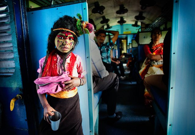 """I was on Durga Puja Festival vacation, travelling on a local train. A boy was singing devotional song and begging for alms. He was guised as a Hindu god, Lord Shiva. This is a common view in Indian trains but this boy was charming, bright and did have a melodious voice. My camera was ready hanging on my neck so I took a picture"". (Photo and caption by Arup Ghosh/2014 Sony World Photography Awards)"
