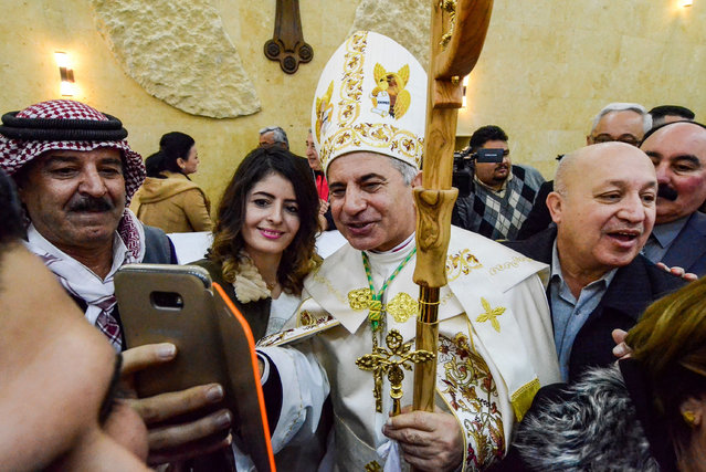 """The new Chaldean Catholic Archbishop Najib Michaeel Moussa (C) uses a cell phone to take a """"selfie"""" photograph with a woman, during his ordination ceremony at St Paul's Cathedral in the eastern part of the northern Iraqi city of Mosul on January 25, 2019. The Iraqi priest who saved a trove of religious manuscripts from the Islamic State group was ordained on January 25 as the Chaldean church's new archbishop of Mosul. The 63-year-old Archbishop Najib Michaeel was inaugurated in a ceremony in attended by Catholic leaders from Iraq and beyond, as well as local officials and residents. (Photo by Zaid al-Obeidi/AFP Photo)"""