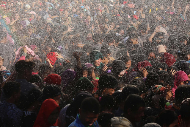 This picture taken on June 7, 2019 shows a large crowd of well-wishers braving the rain as they gather at the residence of Indonesian Vice President Jusuf Kalla in Makassar, to attend his Eid open house reception. Millions of Indonesians will be returning to work after a week-long Eid holidays which saw an exodus from the cities. (Photo by Daeng Mansur/AFP Photo)