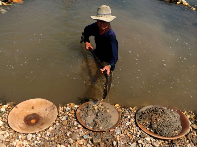 A worker shovels mud from the river as he pans for gold in Lampang. (Photo by Borja Sanchez-Trillo/Getty Images)