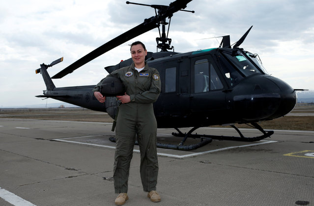 """Ekaterine Kvlividze, 30, a military pilot captain, poses for a photograph in front of a Georgian Air Force UH-1H helicopter in Tbilisi, Georgia, February 22, 2017. Kvlividze joined the Georgian Air Forces in 2007. """"There were some difficulties at the beginning, I felt some irony, cynicism. I felt they did not appreciate me. But, thank God, during the last 10 years society has changed and nowadays a woman pilot is a normal thing"""". (Photo by David Mdzinarishvili/Reuters)"""