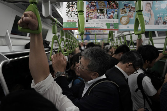 In this Tuesday, May 21, 2019, photo, a man reacts in a packed Yamanote Line train during evening rush hours in Tokyo. Want to take a glimpse of daily life in downtown Tokyo? Take a ride on the Yamanote loop line. For most Tokyoites, the line means an incredibly punctual and efficient transportation system for commuting. For tourists, it offers a glimpse into the life of ordinary people living in the city. (Photo by Jae C. Hong/AP Photo)
