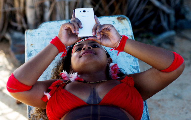 A native Brazilian watches her mobile phone, during the Indigenous Youth Games of Pataxos nation in Santa Cruz de Cabralia, Bahia state, Brazil, April 17, 2016. (Photo by Roosevelt Cassio/Reuters)