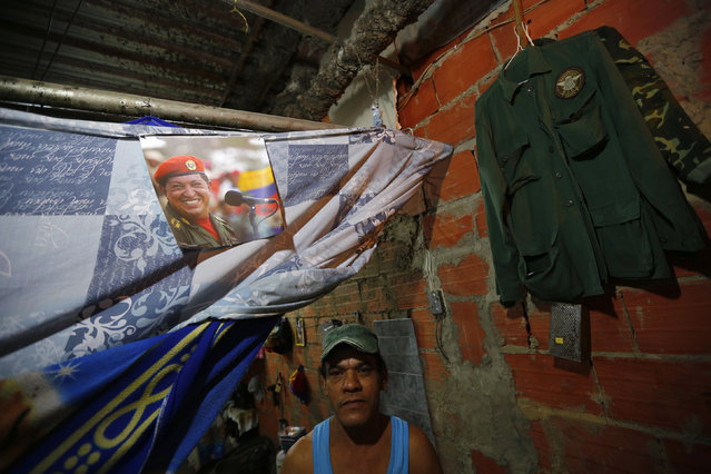 """Jose Aular poses next to a portrait of Venezuela's late President Hugo Chavez in his apartment inside the """"Tower of David"""" skyscraper in Caracas February 6, 2014. (Photo by Jorge Silva/Reuters)"""