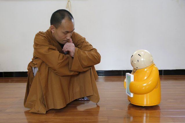 Master Xianfan looks at robot monk Xian'er as he demonstrates the robot's conversation function during a photo opportunity in Longquan Buddhist temple on the outskirts of Beijing, April 20, 2016. (Photo by Kim Kyung-Hoon/Reuters)