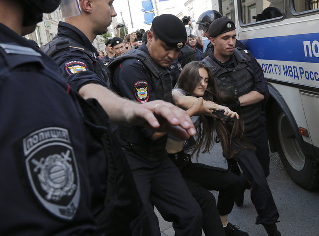 Police officers detain a woman prior to an unsanctioned rally in the center of Moscow, Russia, Saturday, July 27, 2019. OVD-Info, an organization that monitors political arrests, said about 50 people had been detained by 1:30 p.m. Saturday (1030 GMT), a half-hour before the protest against the exclusion of opposition figures from the ballot for city council elections was to start. (Photo by Alexander Zemlianichenko/AP Photo)