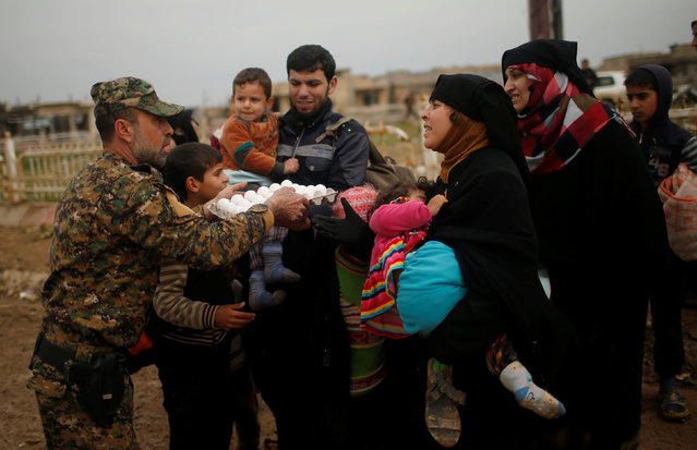 Displaced Iraqis fleeing their homes receive food as Iraqi forces battle with Islamic State militants, in western Mosul, Iraq March 18, 2017. (Photo by Suhaib Salem/Reuters)