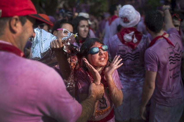 A young woman is drenched in wine during the Batalla de Vino (Wine Battle) in Haro, northern Spain June 29, 2015. (Photo by Vincent West/Reuters)