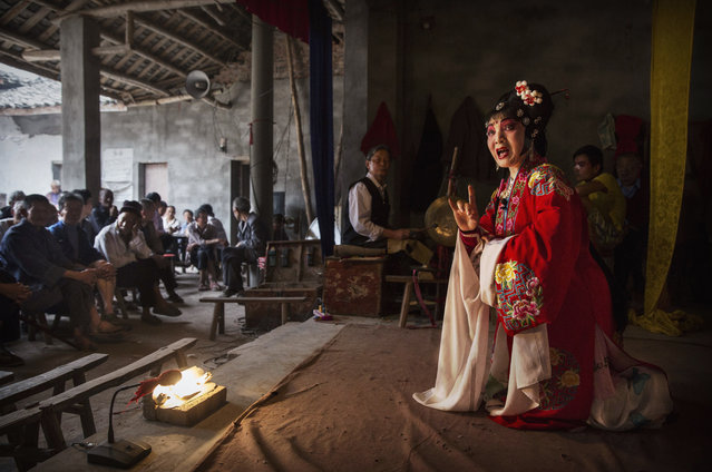 Sichuan Opera actor Lin Lijuan, left, 69 years, of the Jinyuan Opera Company performs for villagers at the Dongyue Temple on May 3, 2016 in Cangshan, Sichuan province, China. (Photo by Kevin Frayer/Getty Images)