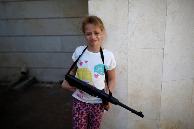 A girl holds a rifle during an event in remembrance of the upcoming Victory Day, marking the anniversary of the Allied victory over Nazi Germany, in the southern city of Ashdod, Israel, May 7, 2016. (Photo by Amir Cohen/Reuters)