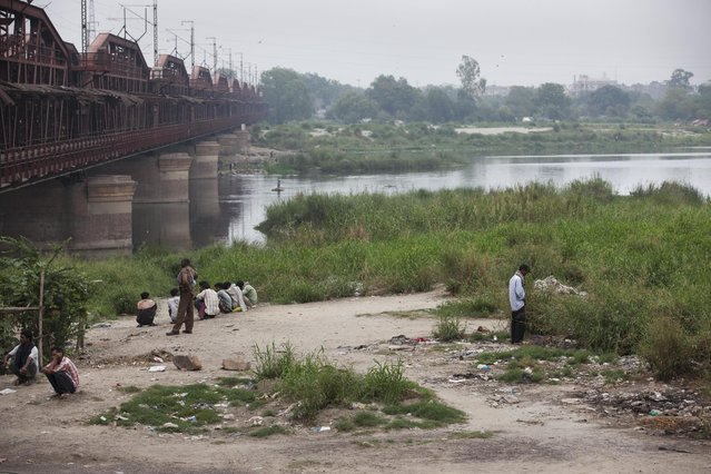 An Indian rickshaw driver urinates on the banks of the River Yamuna in New Delhi, India, Tuesday, June 30, 2015. Toilets are taken for granted in the industrialized West, but still are a luxury for a third of the world's people who have no access to them, according to a report by the World Health Organization and UNICEF released Tuesday. (Photo by Tsering Topgyal/AP Photo)