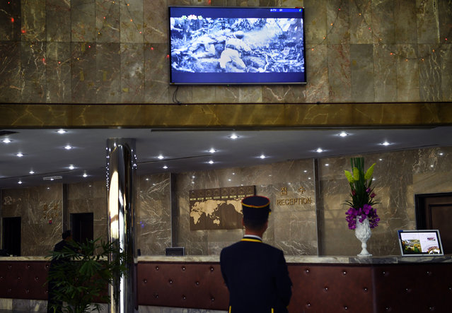 A bell man at the Yanggakdo Hotel where foreigners stay watches a film featuring American casualties and hitler from World War II in Pyongyang, North Korea on May 5, 2016. (Photo by Linda Davidson/The Washington Post)