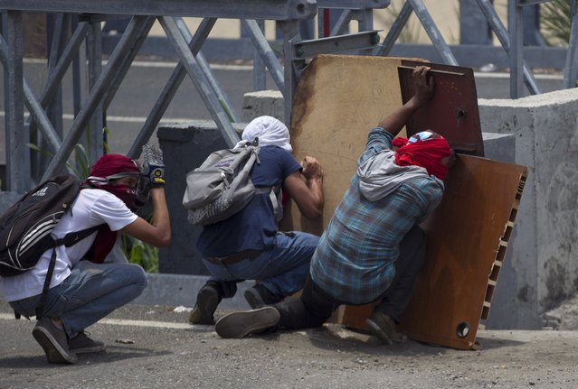 Demonstrators take cover during clashes with the Bolivarian National Gaurd during a protest in Caracas, Venezuela, Monday, April 10, 2017. Opponents of President Nicolas Maduro protested on the streets of the capital as part of an ongoing protest movement that shows little sign of losing steam. (Photo by Ariana Cubillos/AP Photo)