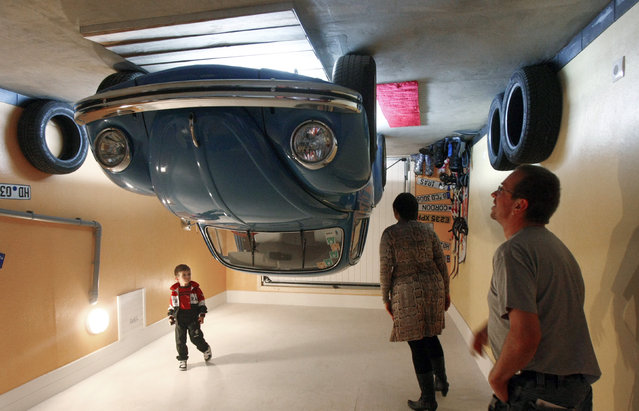 People stand in the garage of a house, which was built upside down by Polish architects Irek Glowacki and Marek Rozhanski, in the western Austrian village of Terfens May 5, 2012. (Photo by Dominic Ebenbichler/Reuters)