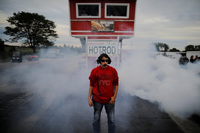 Hunter Dye stands amid smoke from tires in the water box at the starting line at the Great Lakes Dragaway in Union Grove, Wisconsin, September 7, 2019. (Photo by Brian Snyder/Reuters)