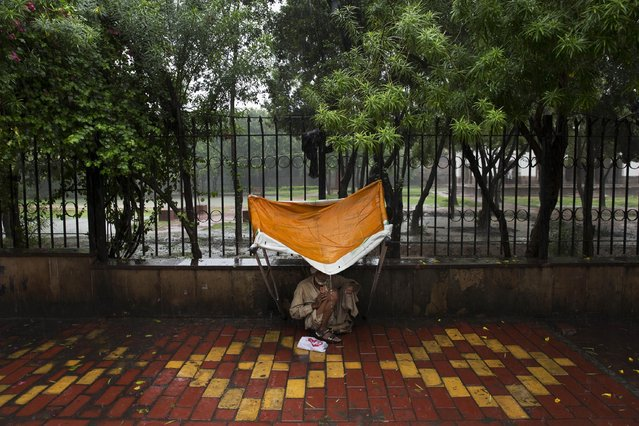 An Indian homeless man takes shelter during monsoon rains in New Delhi, India, Saturday, July 11, 2015. Tens of thousands of impoverished people live on the streets in New Delhi, where they struggle with constant hunger and extreme weather while sleeping nights next to busy intersections and roads. (Photo by Bernat Armangue/AP Photo)